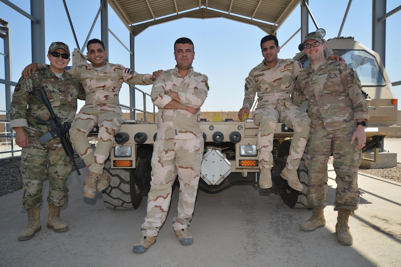 Senior Airman Juan Calderon (far left) and Staff Sgt. Michael Shoemaker (far right), 370th Air Expeditionary Advisory Group air advisors, pose for a photo with Iraqi Air Force airmen at Al Muthana Air Base, April 23, 2018. The air advisors work with their Iraqi counterparts to assist with training and safety protocols specific to their expertise. (Air Force photo by Staff Sgt. William Banton)