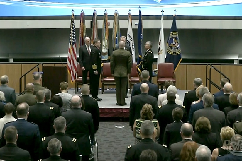 Defense leaders take part in a ceremony.