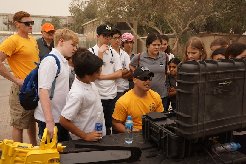 U.S. Army Staff Sgt. Richard Lee, center, assigned to the 74th Engineer Dive Detachment, showing the students from the American School of Kuwait a diver welding underwater with the remote operated vehicle (or ROV) from Seabotix ant Kuwait Naval Base, Kuwait, March 9, 2018.