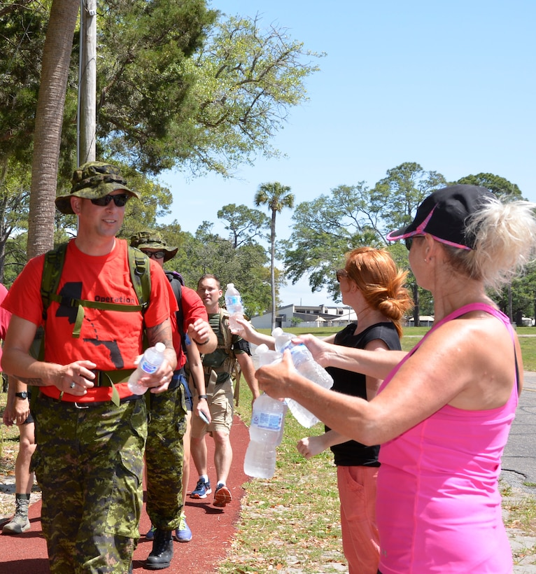 "TYNDALL AIR FORCE BASE, Fla.  - Members of the 1st Air Force Key Spouses Club hand out water to participants along the route of the second annual ""5K Ruck March for Hunger"" May 4 here.