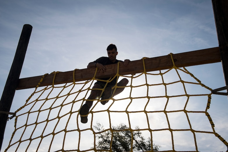 A Moody Mud Run participant climbs a rope obstacle, May 5, 2018, in Ray City, Ga. Participants trekked 4.6 miles through the mud, water and 29 obstacles that made up the course. This is the fifth year Moody has hosted the event and more than 800 patrons participated. (U.S. Air Force photo by Senior Airman Janiqua P. Robinson)