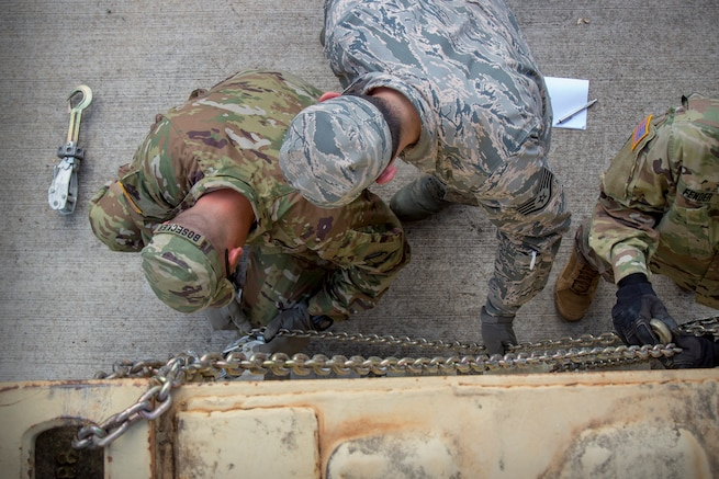 Staff Sgt. Cespedes Maranon, 69th Aerial Port Squadron cargo technician, teaches a member of the Army's 25th Infantry Division how to properly secure cargo using chains and devices at Wheeler Army Airfield, Hawaii, April 11, 2018. Members of the 69 APS traveled to Hawaii to conduct joint training with the Army to be better prepared for future deployment challenges. (U.S. Air Force photo by Senior Airman Jeron Fyfield)