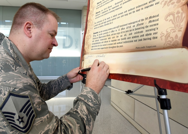 Master Sgt. Mark Kroll, 59th Medical Operations Group post-anesthesia care unit flight chief, signs a proclamation during National Nurse Week 2018 at Wilford Hall Ambulatory Surgical Center, Joint Base San Antonio-Lackland, Texas. The 59th Medical Wing kicked off the event with the signing of a new proclamation declaring May 6-12 as Nurse and Medical Technician Appreciation week. (U.S. Air Force photo by Staff Sgt. Kevin Iinuma)