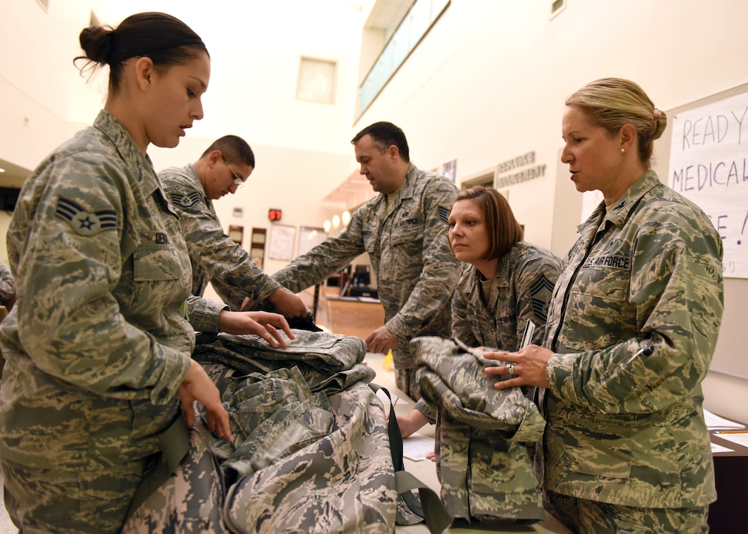 Col. Kristen Beals, 359th Medical Group Commander, and Chief Master Sgt. Kristy Earls, 359th MDG superintendent, inspects personal mobility bags during a recall at the Joint Base San Antonio-Randolph clinic, May 3. The recall was conducted to measure military preparedness, operational readiness mindset and to support the Air Force Medical Service and Defense Health Agency goals of a Medically Ready Force and a Ready Medical Force. (U.S. Air Force photo by Staff Sgt. Kevin Iinuma)