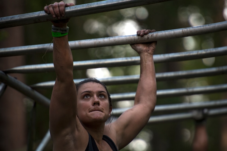 A Moody Mud Run participant crosses a monkey bars obstacle, May 5, 2018, in Ray City, Ga. Competitors trekked 4.6 miles through the mud, water and 29 obstacles that made up the course. This is the fifth year Moody has hosted the event and more than 800 patrons participated. (U.S. Air Force photo by Staff Sgt. Ryan Callaghan)