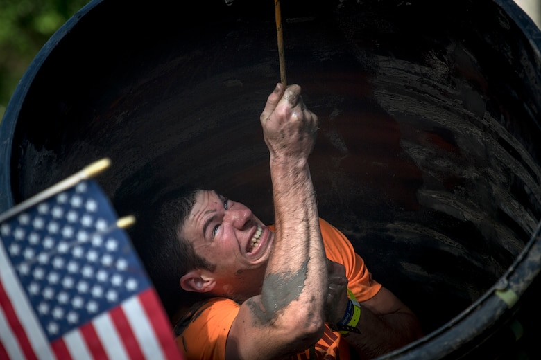 A Moody Mud Run participant pulls himself through a tube obstacle, May 5, 2018, in Ray City, Ga. Competitors trekked 4.6 miles through the mud, water and 29 obstacles that made up the course. This is the fifth year Moody has hosted the event and more than 800 patrons participated. (U.S. Air Force photo by Staff Sgt. Ryan Callaghan)