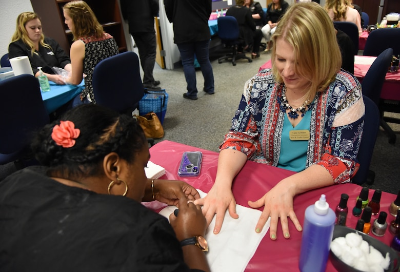 Tristan Mitchell, Virginia College cosmetology student, gives Cara Grittner, spouse of U.S. Air Force Tech. Sgt. Scott Grittner, Mathies NCO Academy instructor, a manicure during Pamper Me Day in the Sablich Center at Keesler Air Force Base, Mississippi, May 3, 2018. The 81st Force Support Squadron Airman & Family Readiness Center has hosted the event for the past 14 years, offering military spouses information and business booths, free manicures, makeup tips and giveaways. (U.S. Air Force photo by Kemberly Groue)