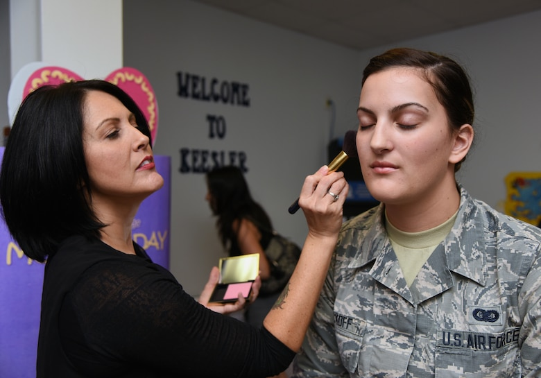 Jennifer Davis, Este Lauder counter manager, applies blush on U.S. Air Force Airman 1st Class Gabrielle Wyckoff, 81st Force Support Squadron commander support staff, during Pamper Me Day in the Sablich Center at Keesler Air Force Base, Mississippi, May 3, 2018. The 81st FSS Airman & Family Readiness Center has hosted the event for the past 14 years, offering military spouses information and business booths, free manicures, makeup tips and giveaways. (U.S. Air Force photo by Kemberly Groue)
