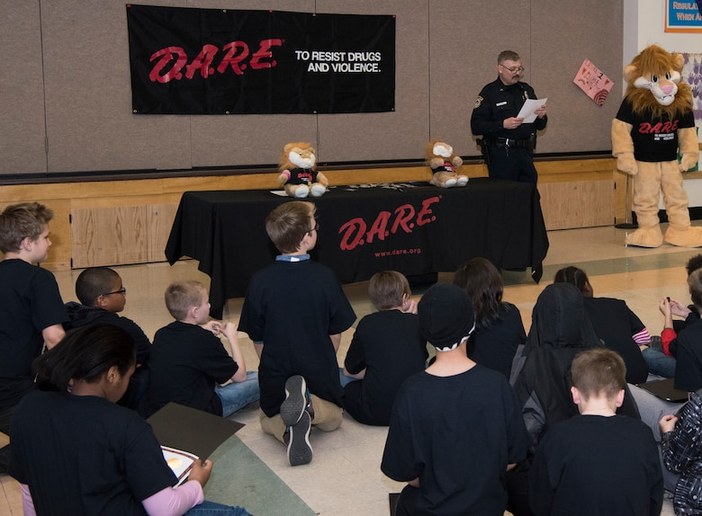 Michael J. Crerend, lead police officer with the 673d Security Forces Squadron and Drug Abuse Resistance Education officer, reads to the students from the D.A.R.E. program at Ursa Major Elementary School at Joint Base Elmendorf-Richardson, Alaska, May 2, 2018. D.A.R.E. is a program designed to provide students with the knowledge and tools they need to resist drugs, alcohol and other high-risk behaviors.