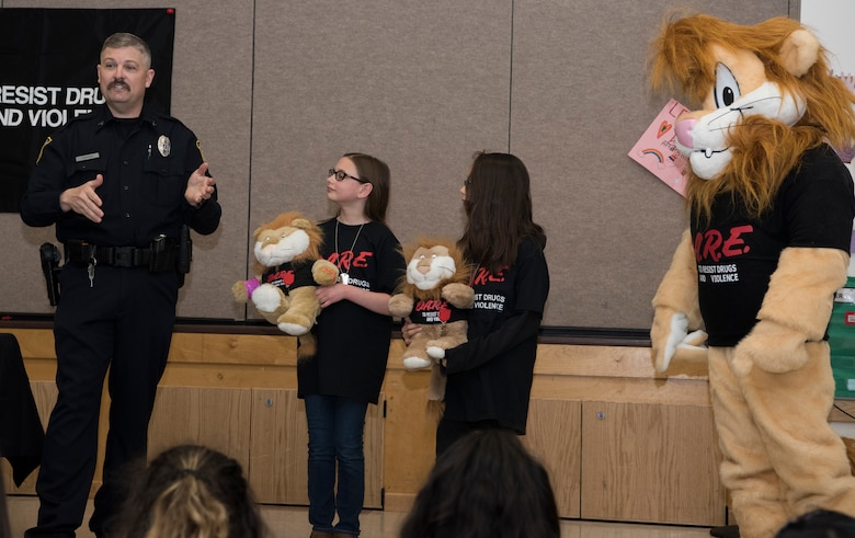 Michael J. Crerend, lead police officer with the 673d Security Forces Squadron and Drug Abuse Resistance Education officer, recognizes two students from the D.A.R.E. program for their achievements at Ursa Major Elementary School at Joint Base Elmendorf-Richardson, Alaska, May 2, 2018. D.A.R.E. is a program designed to provide students with the knowledge and tools they need to resist drugs, alcohol and other high-risk behaviors.