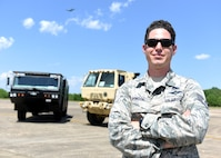A male in uniform stands on a bright flightline in front of two vehicles.