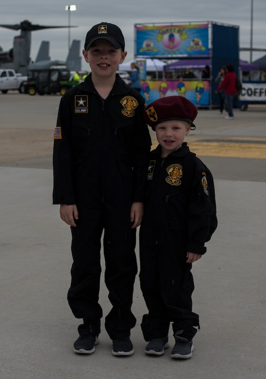 Landon Biggs and his brother, New Jersey boys, pose for a picture during the 2018 Power in the Pines Open House and Air show on Joint Base McGuire-Dix-Lakehurst, N.J., May 6, 2018. Landon travels with his family throughout the Northeastern U.S. to watch the U.S. Army Golden Knights perform. He and his brother wear flight suits identical to the Golden Knights and dream of being on the team one day. (U.S. Air Force photo by Airman Ariel Owings)