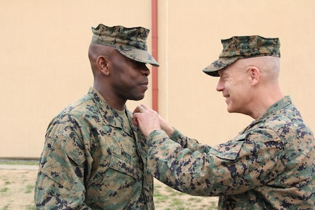 U.S. MARINE CORPS BASE, CAMP MUJUK – Maj. Gen. Patrick J. Hermesmann (RIGHT), commander of U.S. Marine Corps Forces Korea, pins Master Sgt. Olatokunbo A. White, MARFORK communications chief, to his current rank during his promotion and reenlistment ceremony here, May 1.  White's hometown is Norfolk, Va. and he has served at the Expeditionary Strike Group II, MARFORCOM, and has served multiple times at MARFORK. (Official U.S. Marine corps photo by Sgt. Nathaniel Hanscom/Released)