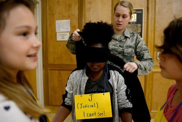 A young girl gets a black scarf tied around her eyes by a woman in the Airman Battle Uniform and two girls smile at the edge of the photo.