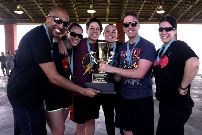 The 19th Airlift Wing's legal office is holding their first place trophy after winning the CLEAR Challenge competition.