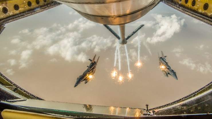Two jets, framed by an opening in an aircraft in front of them, fire flares while in flight.