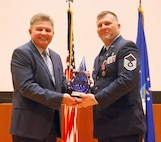 655th Intelligence, Surveillance and Reconnaissance Chief Master Sgt.David L. Wright (left) presents Unit Training Manager and Unit Deployment Manager Master Sgt. Todd Cook a gift from the unit at his retirement ceremony, here, April 21, 2018. Cook retired after 23 years of service. (U.S. Air Force photo/2nd Lt. Weston Woodward)