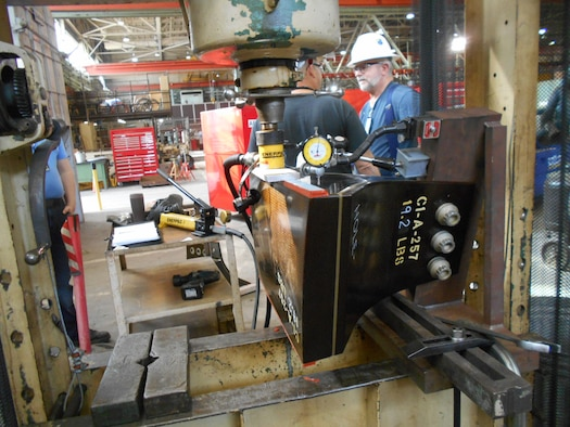 A compressor blade spacer is installed in a hydraulic press machine for load simulations in the Arnold Air Force Base Model and Machine Shop. Machinists recently aided Propulsion Wind Tunnel 16T personnel in the completion of compressor blade spacer testing.