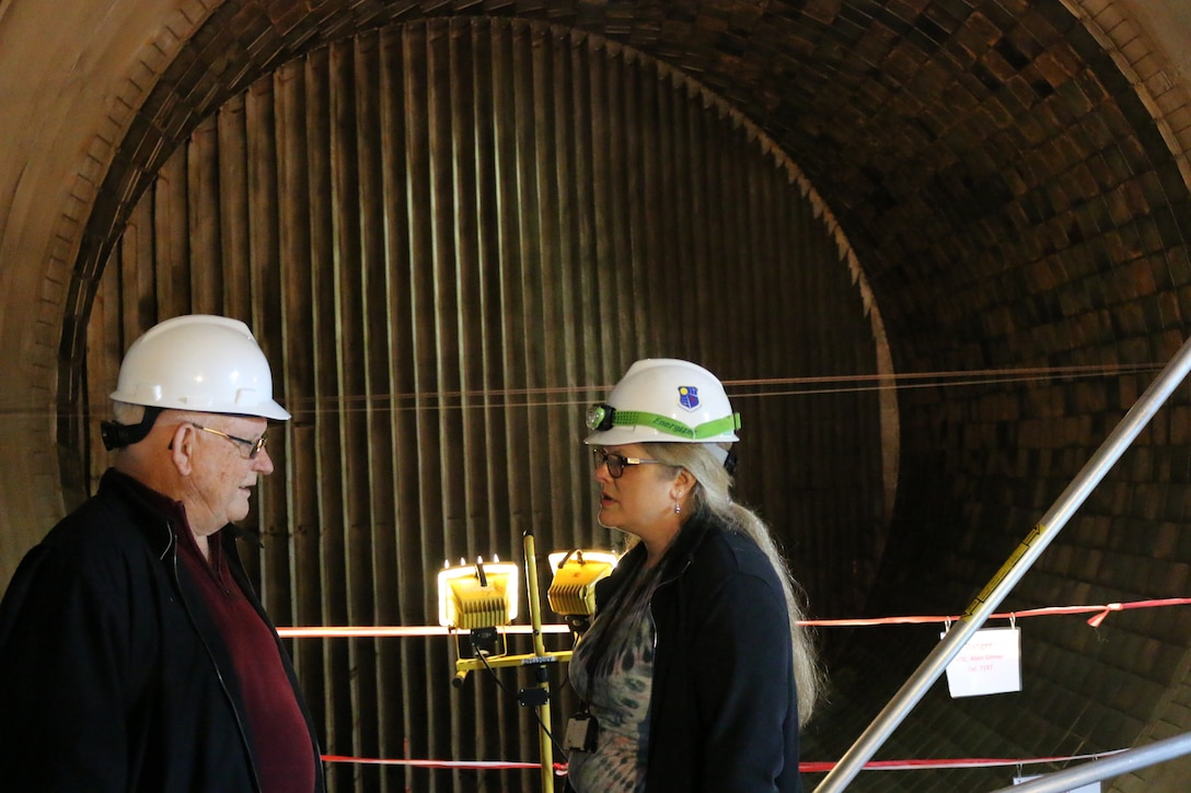 With the wind tunnel itself serving as the backdrop, AEDC retiree Bill Comer, left, discusses the early days of Propulsion Wind Tunnel 16S with engineer Valerie Davenport, a member of the core engineering team assigned to the 16S Return to Service project. Comer was one of eight retirees who recently visited Arnold Air Force Base to offer their input and knowledge as current employees work to return to 16S to service. (U.S. Air Force photo/Bradley Hicks)