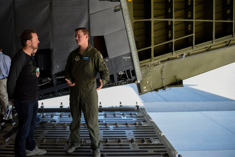 Senior Airman Guy Crawford, 9th Airlift Squadron C-5M Super Galaxy loadmaster, talks to Kurt Busch, driver of the No. 41 Stewart-Haas Racing Ford Fusion car, aboard a C-5M May 3, 2018, at Dover Air Force Base, Del. Along with a tour of the aircraft, Busch also had the chance to fly a C-5 simulator. (U.S. Air Force photo by Airman 1st Class Zoe M. Wockenfuss)