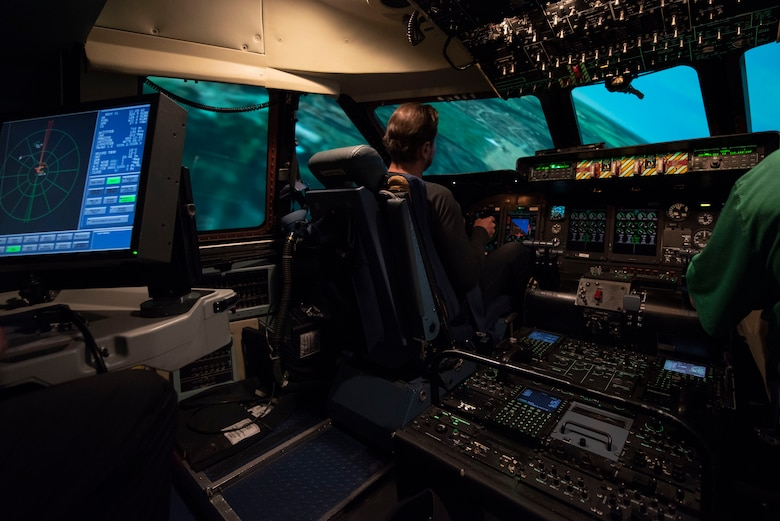 Kurt Busch, driver of the No. 41 Stewart-Haas Racing Ford Fusion car, flies in a C-5M simulator May 3, 2018, at Dover Air Force Base, Del. Along with the C-5, Busch also flew a C-17 Globemaster III simulator later that day. (U.S. Air Force photo by Airman 1st Class Zoe M. Wockenfuss)