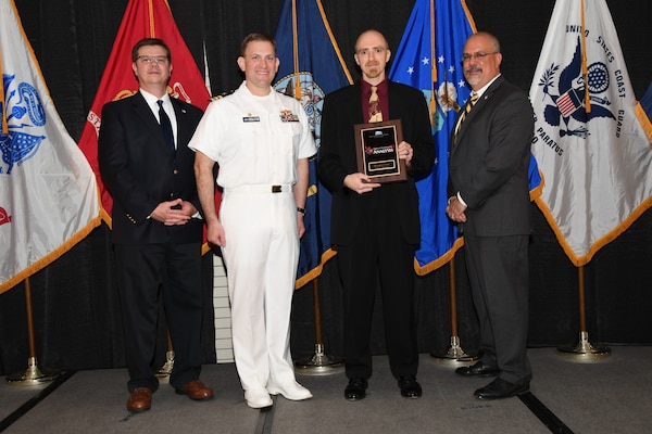 IMAGE: Christopher Glenn is presented the NSWCDD Award of Excellence for Analysis at Naval Surface Warfare Center Dahlgren Division's annual awards ceremony, Apr. 26 at the Fredericksburg Expo and Conference Center.