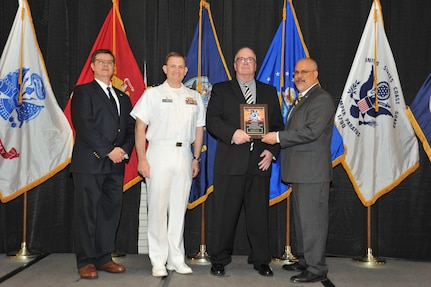 IMAGE: Claiborne Doxey is presented the Award of Excellence for Systems Engineering and Integration at Naval Surface Warfare Center Dahlgren Division's annual awards ceremony, Apr. 26 at the Fredericksburg Expo and Conference Center.  The Award of Excellence for Systems Engineering and Integration was established to recognize individuals who have made a notable and significant impact to NSWCDD through their outstanding performance in systems engineering and integration.