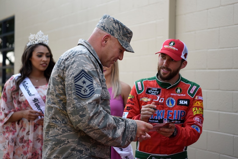 Chief Master Sgt. Anthony Green, 436th Airlift Wing command chief, gets an autograph from Ross Chastain, driver of the No. 15 Premium Motorsports Chevrolet Camaro car, May 4, 2018, at Dover Air Force Base, Del. Several NASCAR drivers attended May's First Friday in Hangar 295 at the Landings to sign autographs and meet some of Team Dover's Airmen. (U.S. Air Force photo by Airman 1st Class Zoe M. Wockenfuss)