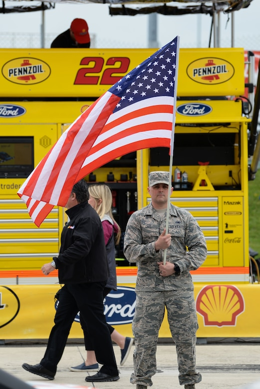 "Airman 1st Class Michael Carl, 166th Maintenance Squadron non-destructive technician, New Castle National Guard Base, Del., holds an American Flag prior to the start of the ""AAA 400 Drive for Autism"" Monster Energy NASCAR Cup Series Race May 6, 2018, at the Dover International Speedway, Del. Carl and other Airmen participated in the race as volunteers and honorary pit crew members. (U.S. Air Force photo by Airman 1st Class Zoe M. Wockenfuss)"