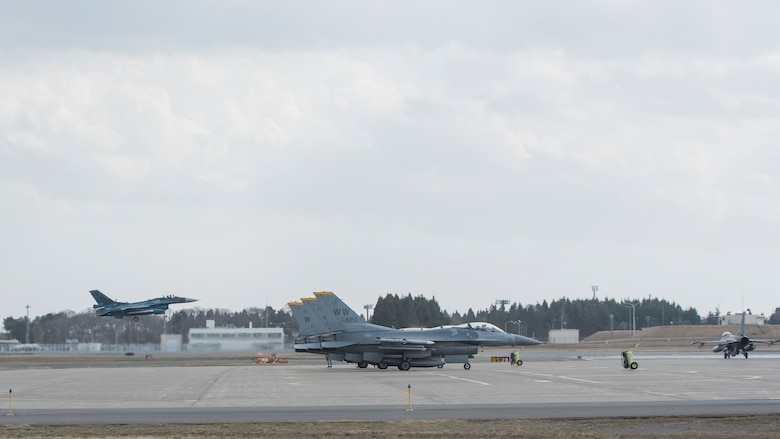 A Japan Air Self-Defense Force F-2 takes flight while a U.S. Air Force F-16 Fighting Falcon taxis on the flight line in preparation for dissimilar air combat tactics operations at Misawa Air Base, Japan, April 12, 2018. DACT is performed between the Japan Air Self-Defense Force and U.S. forces monthly to share knowledge and experience and build camaraderie. (U.S. Air Force photo by Airman 1st Class Collette Brooks)