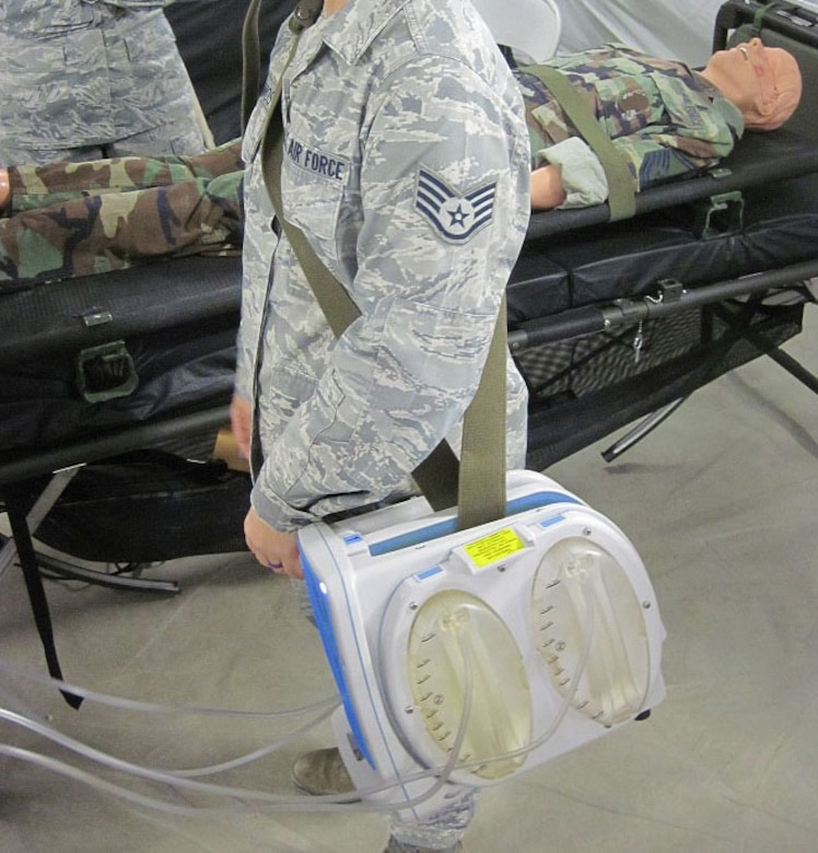 An Airman straps on the multi-channel wound vacuum system during training at the 59th Medical Wing, San Antonio, Texas, Nov. 30, 2016. The multi-channel wound vacuum system, which is used to help promote wound healing on critical patients, is able to replace four single-channel systems. This smaller, more transportable device makes it easier for aeromedical evacuation crews to deliver en route wound care to patients with multiple wounds on the back of an aircraft where space is limited. The Air Force Medical Evaluation Support Activity (AFMESA) team was involved in the development and testing of the multi-channel wound vacuum system, ensuring the device could perform in the operational environment. (Courtesy photo)