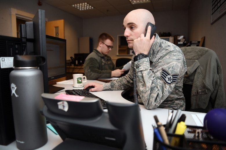 U.S. Air Force Staff Sgt. Zachary Boomer, 100th Force Support Squadron outbound assignments technician, takes a phone call, at RAF Mildenhall, England, April 17, 2018. Airmen in the military personnel flight are responsible for ensuring Airmen across base have their records squared away and are deployment ready. (U.S. Air Force photo by Senior Airman Christine Groening)