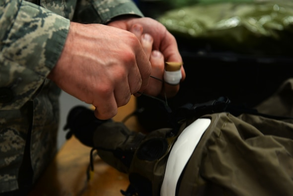 A U.S. Airman from the 100th Operations Support Squadron aircrew flight equipment shop tacks an oxygen mask to secure the threading of a mask lining at RAF Mildenhall, England, April 24, 2018. The AFE shop is the insurance of the aircrew and keeps emergency kits prepared in case of an in-flight emergency. (U.S. Air Force photo by Airman 1st Class Alexandria Lee)