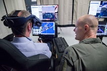 Royal Air Force Air Marshall Sean Reynolds (left), senior officer responsible for personnel and capability of the United Kingdom's RAF and U.S. Air Force Lt. Col. Robert Vicars, Pilot Training Next initiative director, go through a flight simulator at the Pilot Training Next detachment in Austin, Texas, May 3, 2018. Reynolds' visit involved a tour of PTN facilities to better understand how Air Education and Training Command uses existing and emerging technologies to decrease the time and cost of training, without sacrificing depth of learning and strengthened partnerships through the sharing of best practices and mutual interests. (U.S. Air Force photo by Sean Worrell)