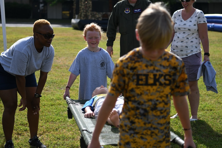 Mackenna and Maxon Richardson, children of U.S. Air Force Lt. Col. Tighe Richardson, 81st Medical Group ophthalmology and refractive surgery chief, perform a litter carry during Operation Hero at Keesler Air Force Base, Mississippi, May 5, 2018. During the event, children had different tasks to complete before getting a tour of a C-130J Hercules . (U.S. Air Force photo by Airman 1st Class Suzie Plotnikov)