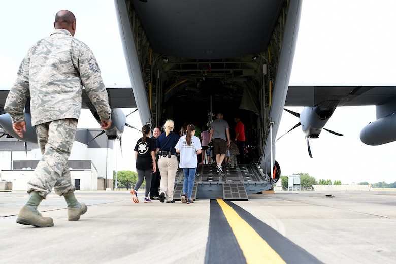 Keesler families enter a C-130J Hercules during Operation Hero at Keesler Air Force Base, Mississippi, May 5, 2018. The event gave military children a glimpse into the lives of deployed military members. (U.S. Air Force photo by Airman 1st Class Suzie Plotnikov)