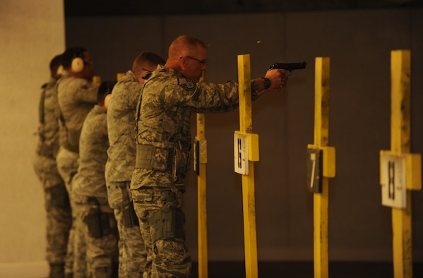 Security Forces Squadron Airmen fire off M9 pistol rounds for training at Ellsworth Air Force Base, S.D., Oct. 13, 2015. Airmen are trained on proper weapon control to ensure that personnel know how to safely and properly operate their weapon for protective uses. (U.S. Air Force photo by Airman Sadie Colbert/Released)