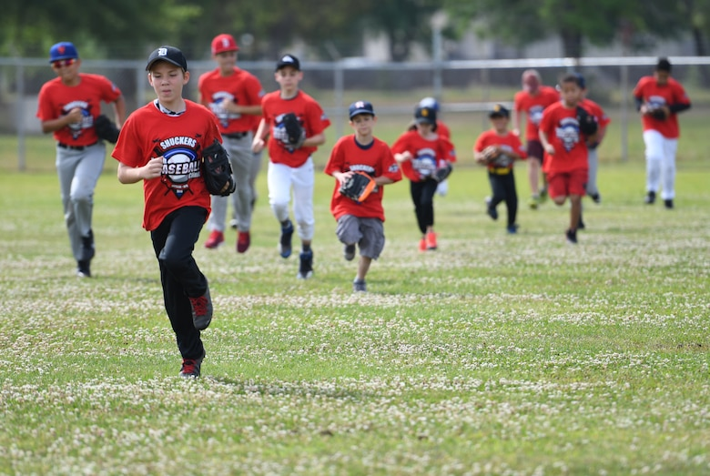 Keesler children run warm-up laps during the Biloxi Shuckers Youth Baseball Clinic on the youth center baseball field at Keesler Air Force Base, Mississippi, May 5, 2018. More than 20 children attended the clinic that provided hitting, pitching, base running and fielding instruction from members of the Biloxi Shuckers minor league baseball team. (U.S. Air Force photo by Kemberly Groue)