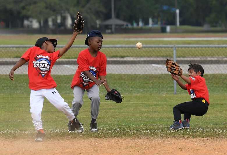 Keesler children try to catch the ball during the Biloxi Shuckers Youth Baseball Clinic on the youth center baseball field at Keesler Air Force Base, Mississippi, May 5, 2018. More than 20 children attended the clinic that provided hitting, pitching, base running and fielding instruction from members of the Biloxi Shuckers minor league baseball team. (U.S. Air Force photo by Kemberly Groue)
