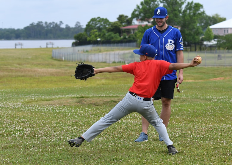 Dylan Moore, Biloxi Shuckers shortstop, assists Andre Torres, son of Andre Torres, 81st Medical Support Squadron defense medical logistics standard support clerk, with pitching techniques during the Biloxi Shuckers Youth Baseball Clinic  on the youth center baseball field at Keesler Air Force Base, Mississippi, May 5, 2018. More than 20 children attended the clinic that provided hitting, pitching, base running and fielding instruction from members of the Biloxi Shuckers minor league baseball team.  (U.S. Air Force photo by Kemberly Groue)