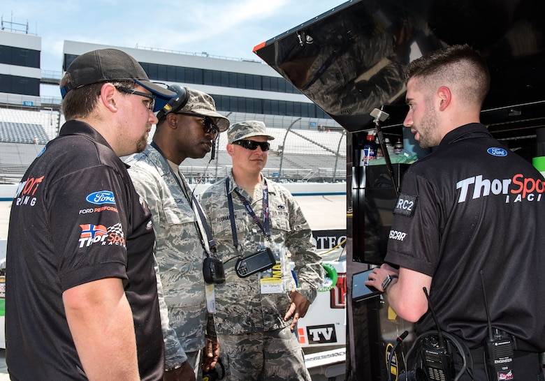 "Tech. Sgt. Mikel Rogers, center left, 436th Civil Engineer Squadron emergency management operations NCO in charge, and Tech. Sgt. Timothy Fluharty, center right, 373rd Training Squadron, Detachment 3, C-5M hydraulics instructor, speak with ThorSport Racing team members Nick Gardiner and Brian Ross, mechanic and race engineer, respectively, May 4, 2018, at Dover International Speedway, Dover, Del. Honorary pit crew members spoke with team members on pit road prior to qualifying for the 19th Annual ""JEGS 200"" race later that afternoon. (U.S. Air Force photo by Roland Balik)"