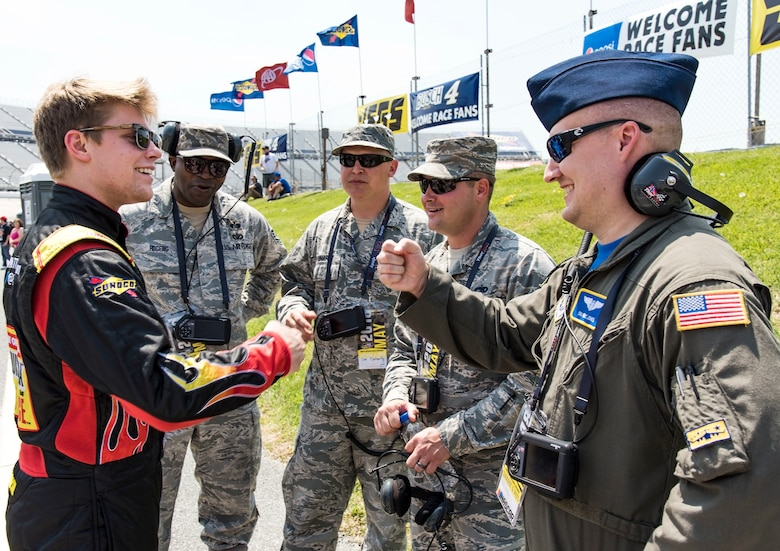 "Myatt Snider, left, NASCAR Camping World Truck Series driver for the No. 13 ThorSport Racing Louisiana Hot Sauce Ford, fist bumps Senior Airman Eric Jones, 3rd Airlift Squadron loadmaster, May 4, 2018, at Dover International Speedway, Dover, Del. Snider spoke with honorary pit crew members prior to qualifying for the 19th Annual ""JEGS 200"" race later that afternoon. (U.S. Air Force photo by Roland Balik)"