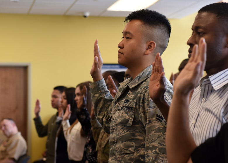 Service members in a court room wait for naturalization.