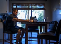 Officer Tim Bull, a Combat Arms Training and Maintenance instructor, sketches a drawing at his kitchen table after work, April 24, 2018, in Palm Bay, Fla. His wife passed away from cancer, 7 years ago. (U.S. Air Force photo by Airman 1st Class Dalton Williams)