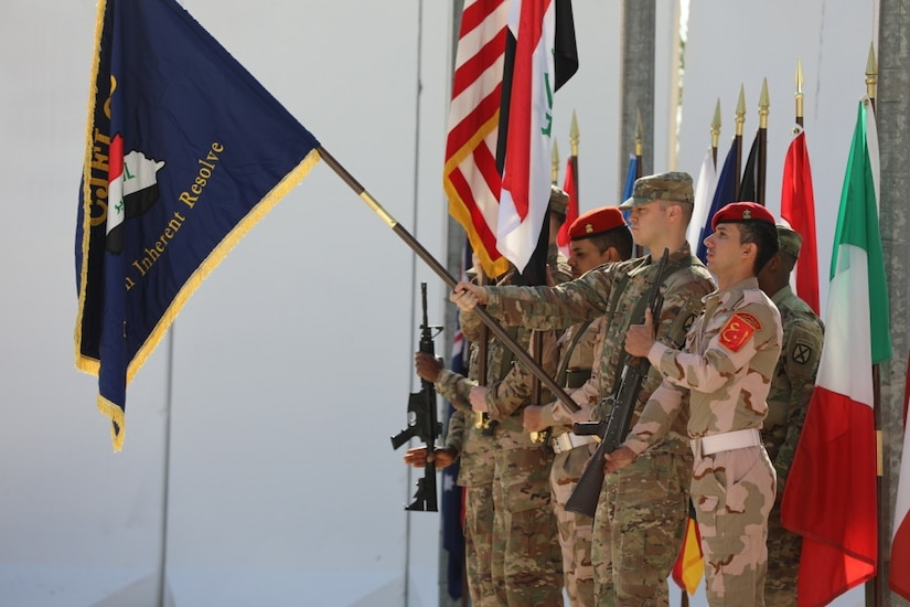 Coalition members with the Combined Joint Forces Land Component Command color guard render a salute during the command's deactivation ceremony at Baghdad, Iraq.