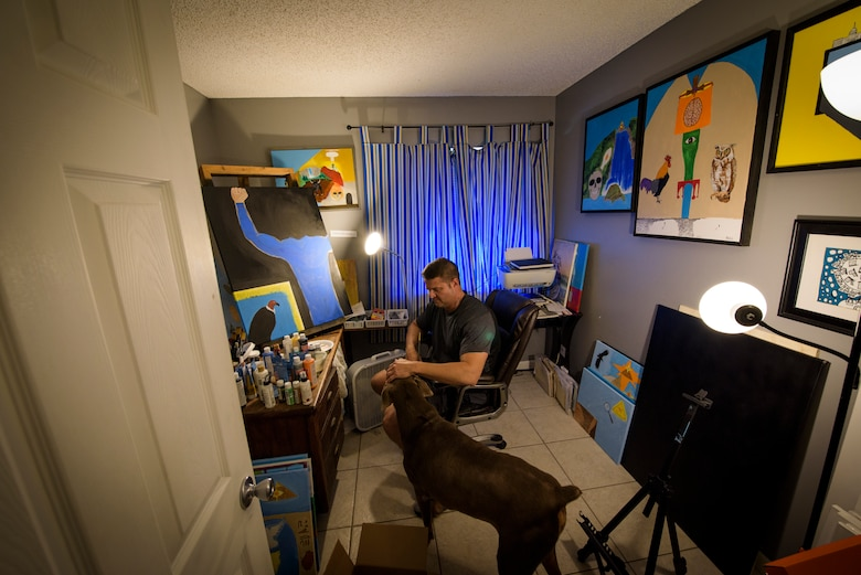 "Officer Tim Bull, a Combat Arms Training and Maintenance instructor, pets his dog, Harley, in between painting, April 24, 2018, in Palm Bay, Fla. Bull is an artist and turned to art as an outlet and release. Bull has a unique art style that combines the surreal with earnest, thought provoking messages. ""It took me 37 years to find out what I wanted to do and this is it"" (U.S. Air Force photo by Airman 1st Class Dalton Williams)"
