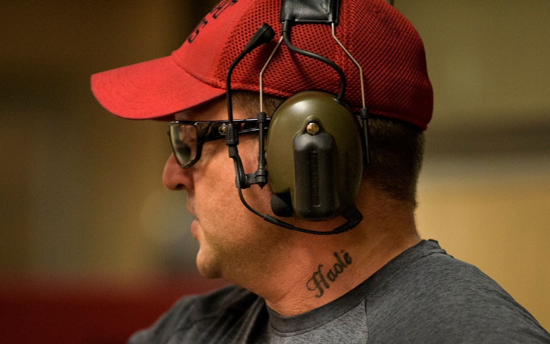 """Officer Tim Bull, a Combat Arms Training and Maintenance instructor, looks out over the firing range, April 25, 2018. Bull has a tattoo on his neck with the word """"haole"""". The word has two meanings according to Bull, meaning both """"breath"""" and being an outsider to Hawaiian culture. Bull also served in the United States Army as an infantryman and was stationed in Hawaii where he met his wife who was a Hawaii native. (U.S. Air Force photo by Airman 1st Class Dalton Williams)"""