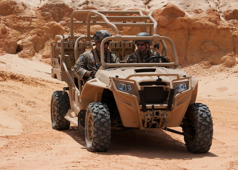 Chief Master Sgt. James Loper, 10th Air Force Command Chief, rides aboard an MRZR military all terrain vehicle with Chief Master Sgt. Brian Bischoff