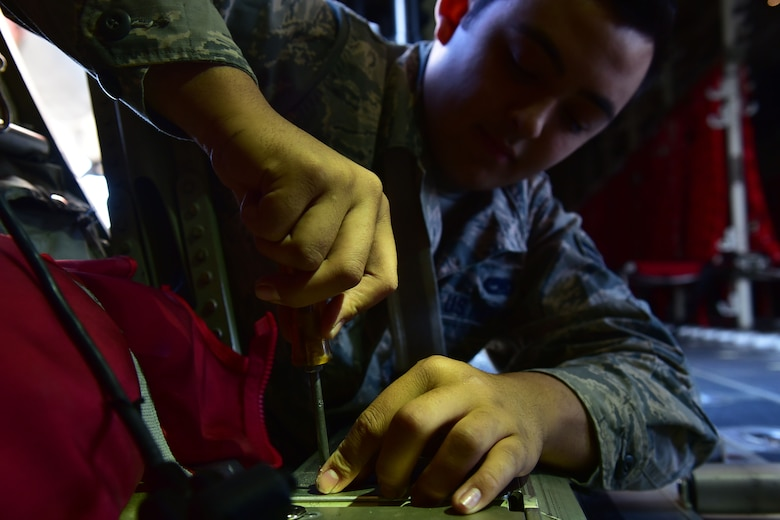 A man unscrews a panel on a C-130J.