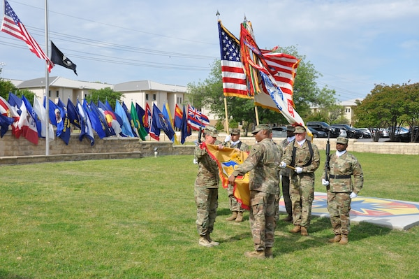 Col. Lynda Armer (left) and Command Sgt. Maj. Darnyell Parker uncase the 418th Contracting Support Brigade colors during a ceremony April 20 at Fort Hood, Texas. The uncasing of organizational colors signals the return from deployment to Afghanistan for the unit. Armer is the 418th CSB commander and Parker is the brigade command sergeant major.